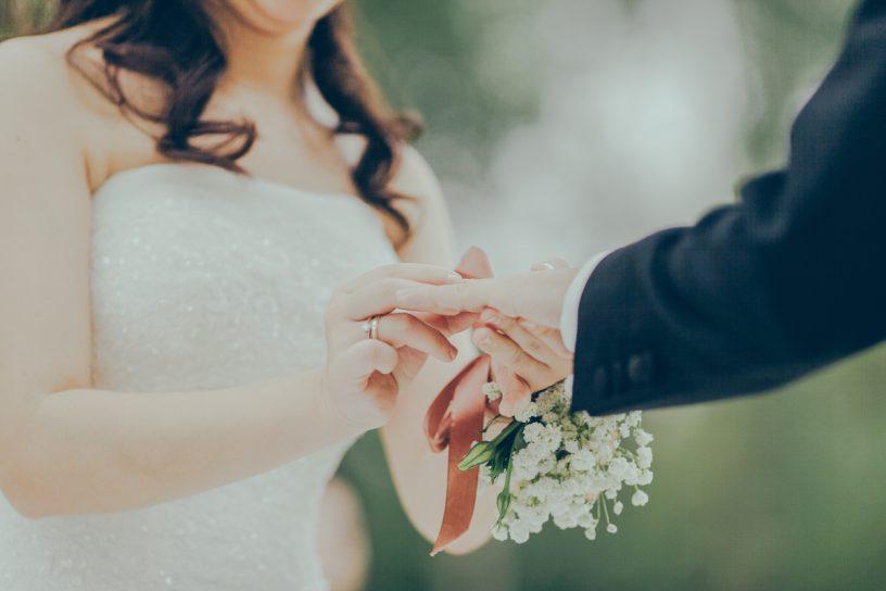 Frau trägt Brautkleid und hält die Hand ihres Ehemanns.