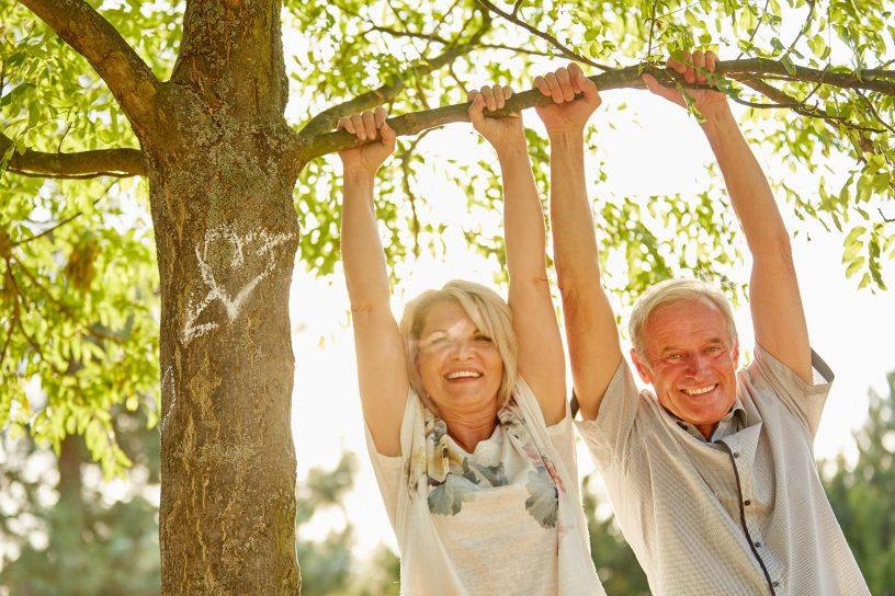 Ein älteres Paar greift nach einem Ast,