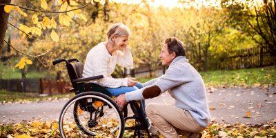 Eine ältere Frau im Rollstühl spricht mit einem jüngeren Mann.