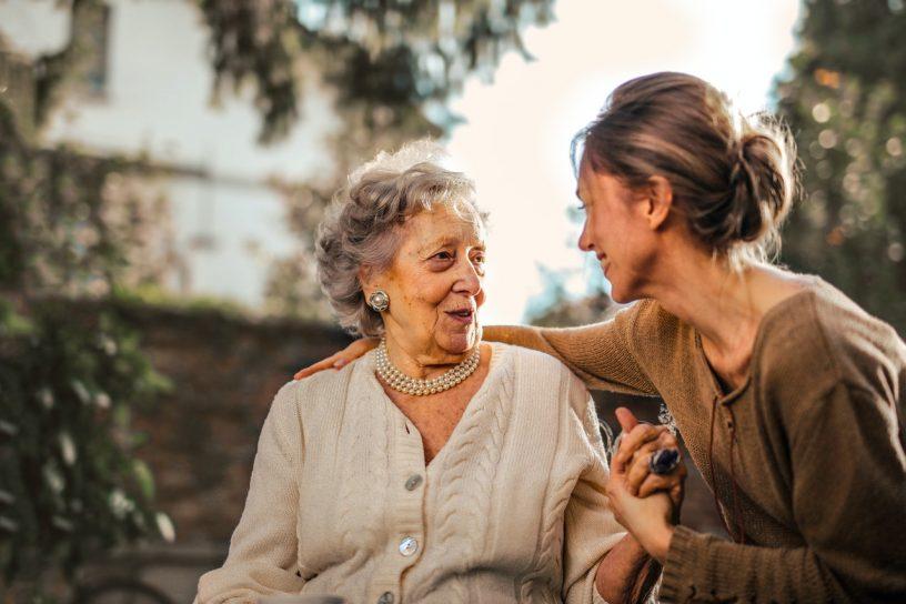 Junge Frau nimmt ihre ältere Mutter in den Arm.