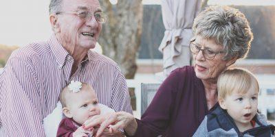 Altes Ehepaar hat seine Enkel auf dem Schoß