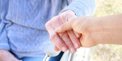 Eine Person im Rollstuhl greift eine andere Hand