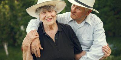 Älteres Ehepaar liegt sich lächelnd in den Armen.