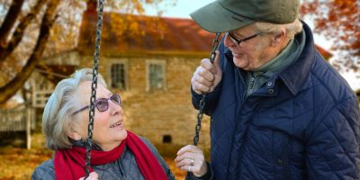 Älterer Mann, der neben seiner Frau steht.